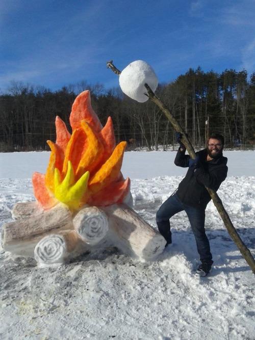 雪でキャンプファイヤーのマシュマロ・ローストをしている男性