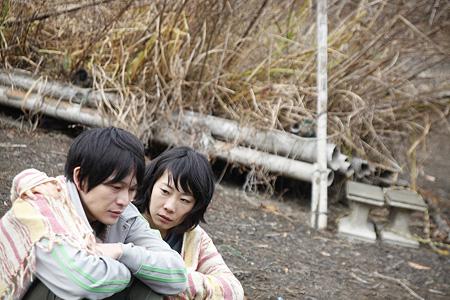 越川道夫 『アレノ』 冒頭のシーンの夫(川口覚)と妻(山田真歩)。雨のシーンなのだが、雨の音だけで実際に雨が降っているように見えないのがちょっと気になった。