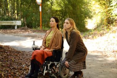 『さようなら』 レオナとターニャ(ブライアリー・ロング)。レオナは足の不具合を直すことができずに車イスを使っている。