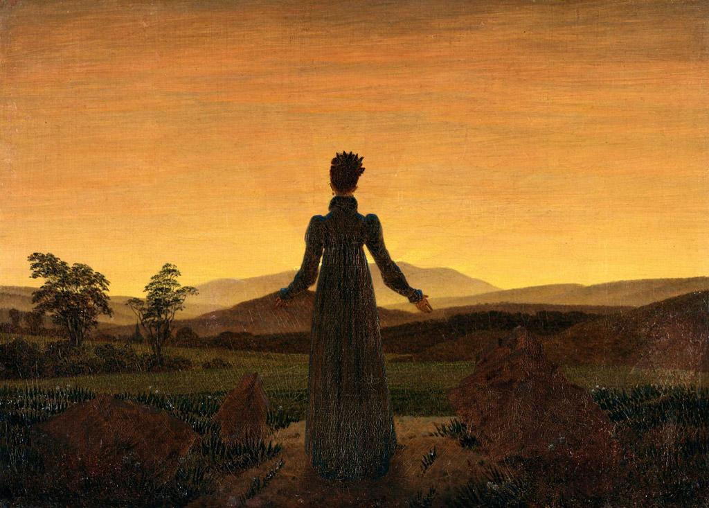 日の出の前に立つ女性