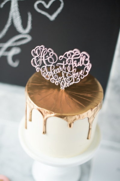 gold-wedding-cake-with-pink-heart-cake-topper.jpg